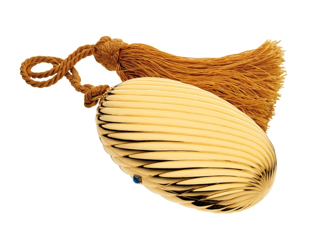 """Melone"" evening bag in gold with sapphire, 1972. The polished and fluted oval case with cabochon sapphire thumbpiece, opening to reveal a fitted mirror, suspended on a golden colour silk cord terminating with a tassel. The interior is fitted with an oval mirror. With a golden coloured silk cord and tassel. Marks: on the rim (interior): ""BVLGARI"" stamped; lozenge with ""750""."