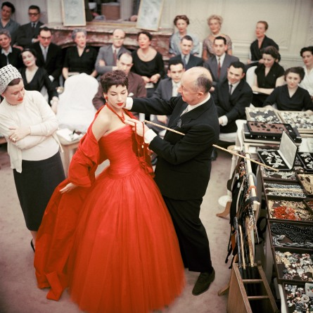 Christian Dior adjusts the accessories to the Zaire dress, on his star model Victoire, during rehearsal for the autumn−winter 1954, haute couture show Photo © Mark Shaw/mptvimages.com