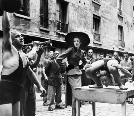 Richard Avedon (1923 – 2004) Elise Daniels with street performers, suit by Balenciaga, Le Marais, Paris, 1948 © The Richard Avedon Foundation