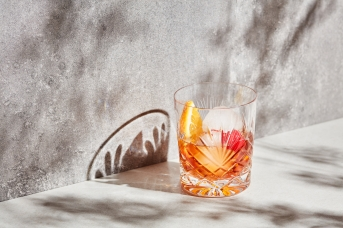 Glass with ice and drink composed on gray in bright sunlight and shadows.